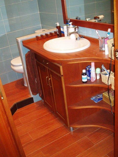 mueble de baño en curva de madera maciza de cerezo barnizado con toallero