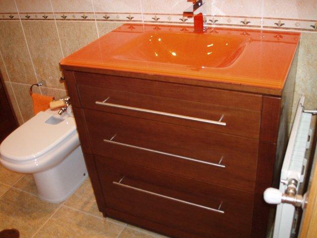 mueble de baño en nogal con lavamanos de cristal naranja y toallero