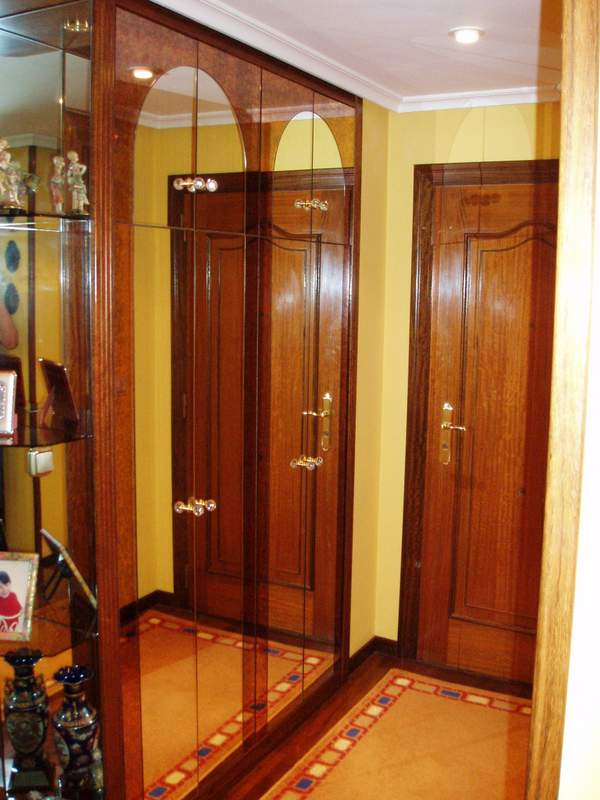 armario empotrado de pasillo de madera y cristal con esquinero