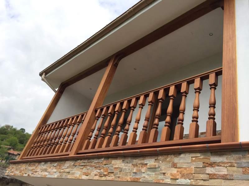 corredor en madera de iroko con balaustres tallados