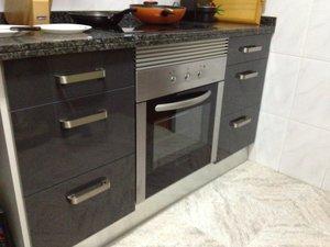 cocina de diseño alto brillo de color gris oscuro o negro con electrodomésticos