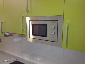 cocina de diseño de color verde con puertas y con electrodomésticos