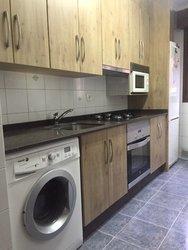 cocina de diseño en color madera, marmol color negro con electrodomésticos