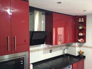 cocina de diseño alto brillo de color rojo y negro con electrodomésticos campana